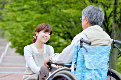 caregiver smiling at elderly man in a wheelchair