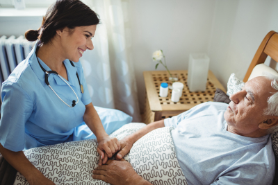 Nurse holding hands of elderly man in bed